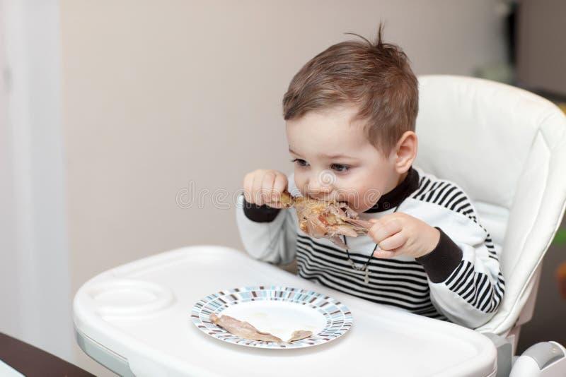 Jongen die eendbeen eten stock afbeelding