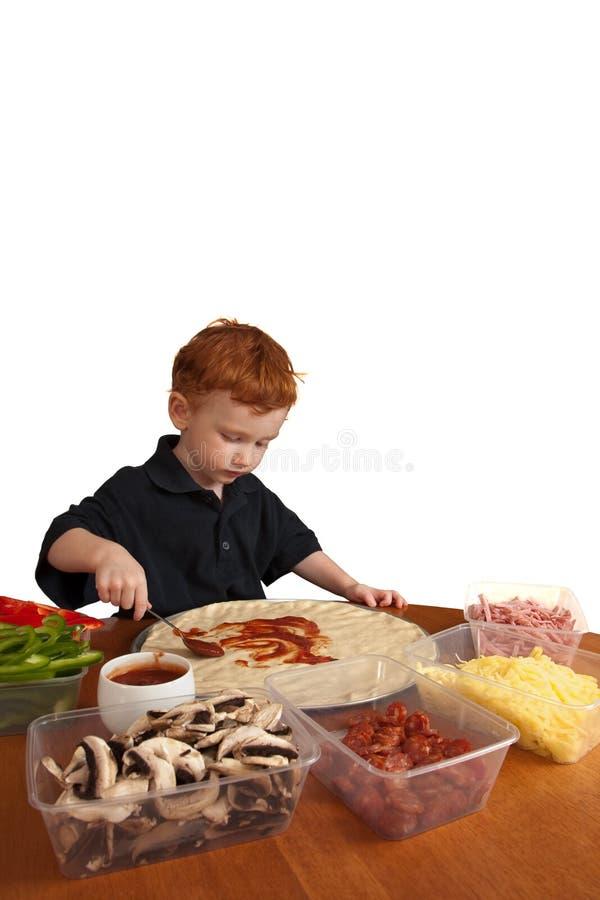Jongen die eigengemaakte pizza voorbereidt stock afbeelding
