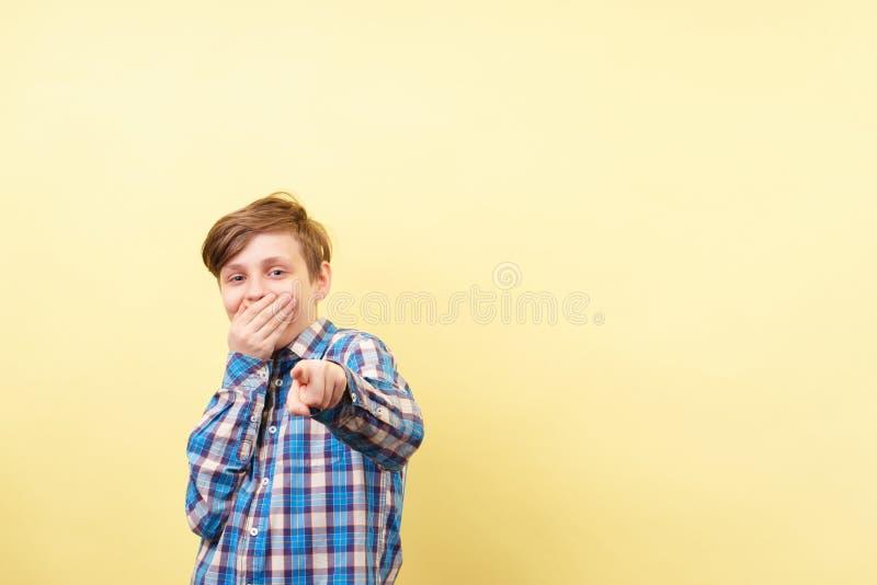 Jongen die en richtend vinger bij kijker bespotten lachen royalty-vrije stock foto