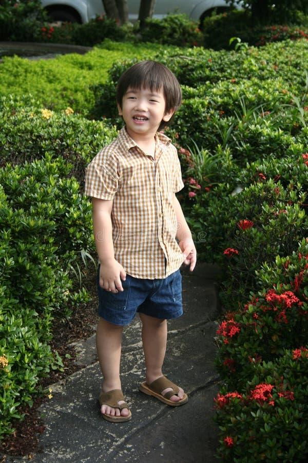 Jongen die gelukkig in de tuin glimlacht royalty-vrije stock foto