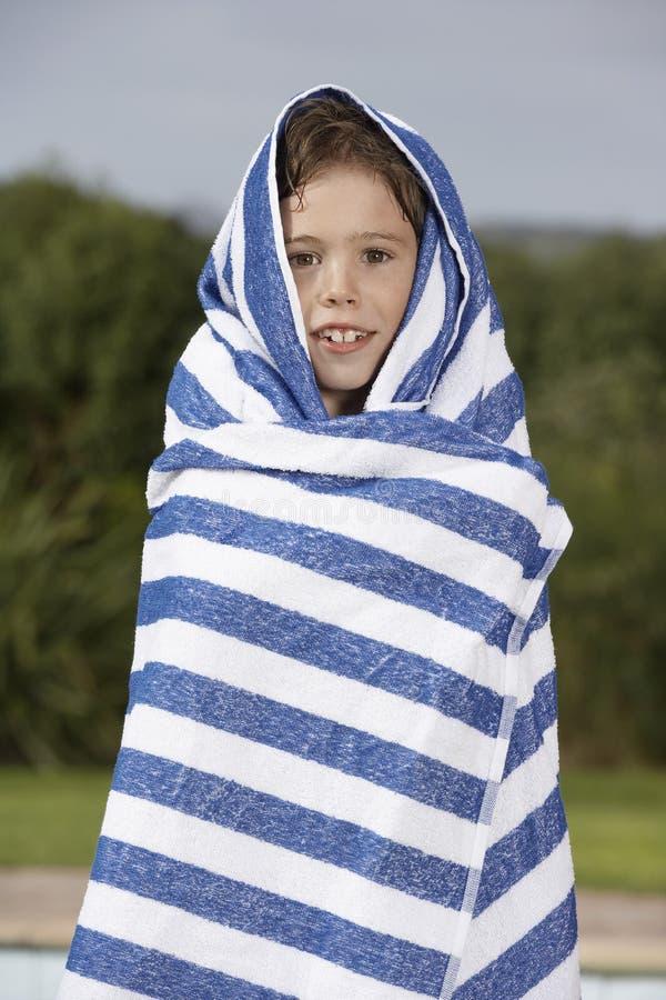 Jongen in Gestreepte Handdoek in openlucht wordt verpakt die royalty-vrije stock afbeelding