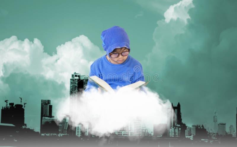 Jongen die glazen dragen die een blauwe hoed dragen, die boek op een wolk dat het drijven, cityscape achtergrond, fantasierijk co royalty-vrije stock fotografie