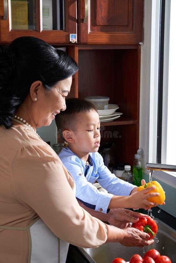 Jongen die grootmoeder in keuken helpen royalty-vrije stock afbeeldingen