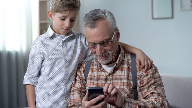 Jongen die grootvader helpen om smartphone, digitale generatiekloof beter te begrijpen stock afbeelding