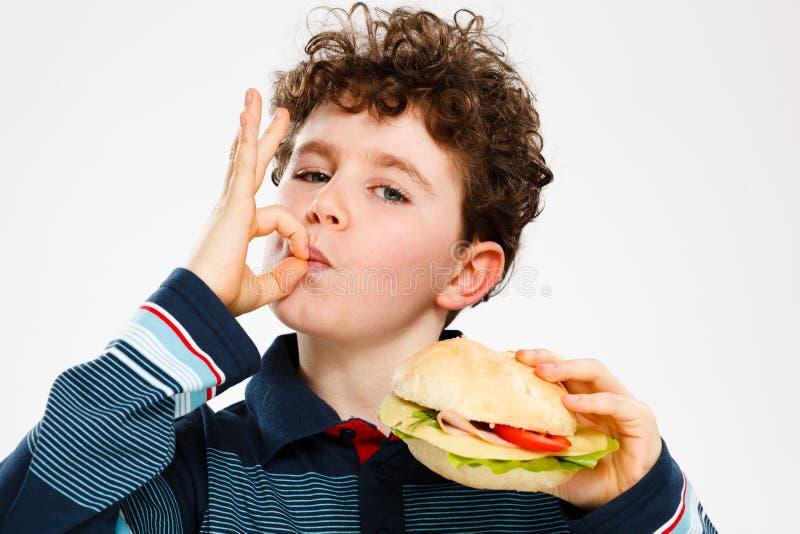 Jongen die grote sandwich eten royalty-vrije stock foto