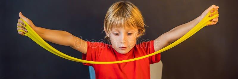 Jongen die hand spelen, speelde speelgoedspeeltje genaamd slik Kinderspel met slijm Kid squeeze and stretching slime BANNER, LONG stock foto