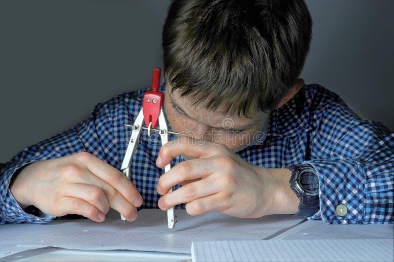 Jongen die het thuiswerk van de wiskundeschool doen stock fotografie
