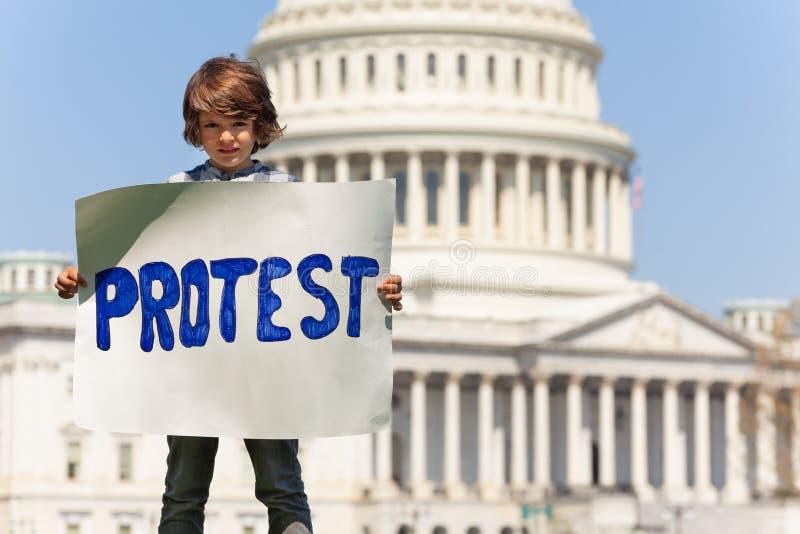 Jongen die holdingsteken vertonen die protest in handen zeggen stock afbeeldingen