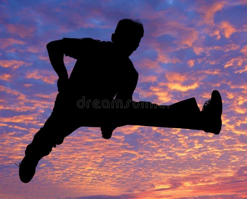 Jongen die hoog in de lucht springt royalty-vrije stock foto's