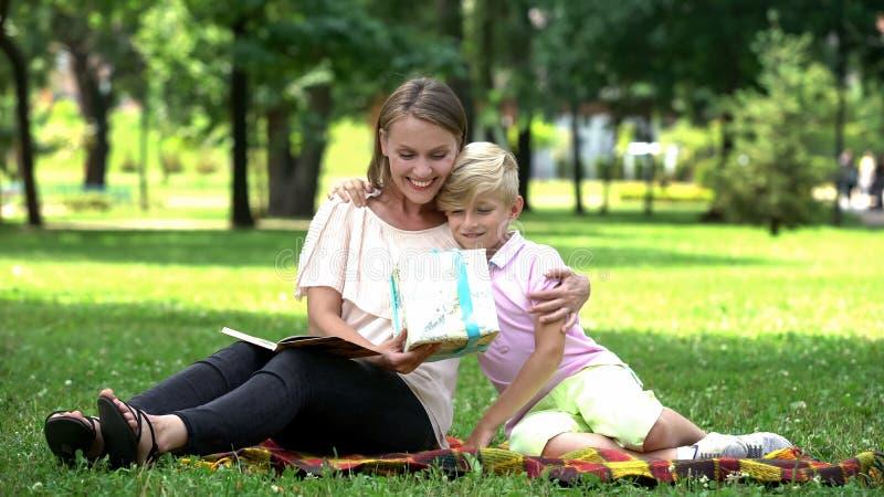 Jongen die huidige doos geven aan moeder, die haar gelukwensen met de dag van de vrouw, houdend van zoon royalty-vrije stock foto