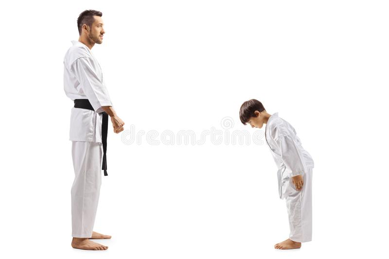 Jongen die in karatekimono aan instructeur buigen stock fotografie