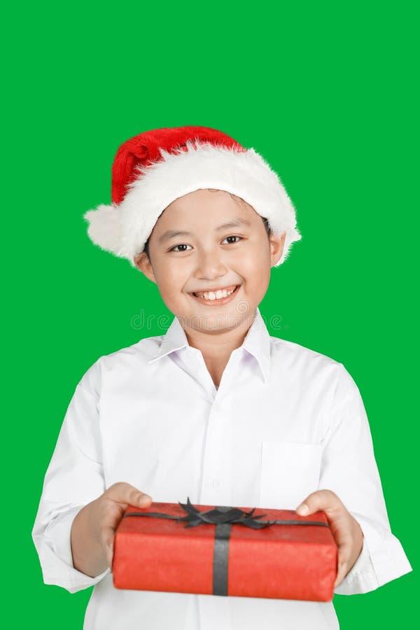 Jongen die Kerstmisgift geven aan camera stock foto