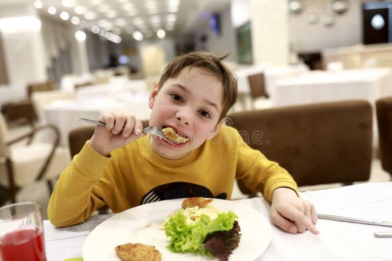 Jongen die kippenkotelet eten stock afbeeldingen