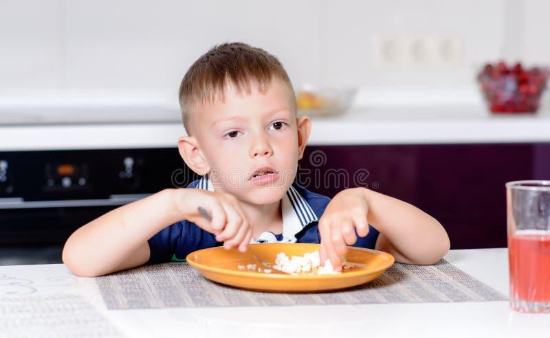 Jongen die Laatste Beet van Voedsel eten bij Keukenlijst stock foto's