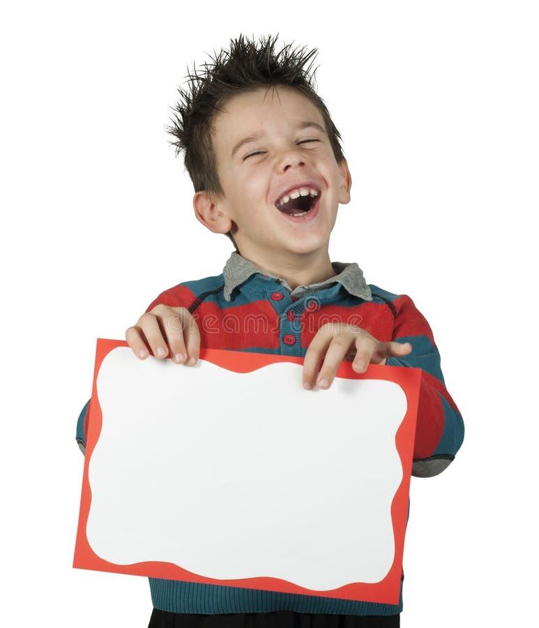 Jongen die lacht en witte raad houdt stock afbeeldingen