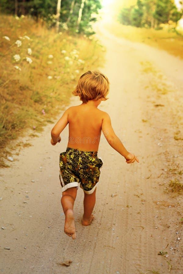 Jongen die langs weg in park lopen, openlucht royalty-vrije stock afbeeldingen