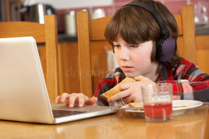 Jongen die Laptop met behulp van terwijl het Eten van Ontbijt stock foto