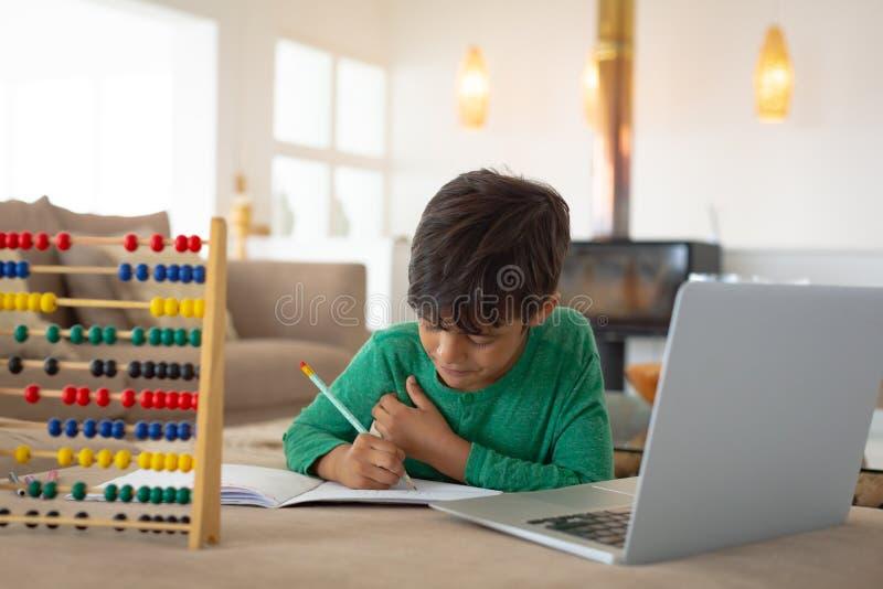 Jongen die laptop met behulp van terwijl thuis het bestuderen in woonkamer royalty-vrije stock foto