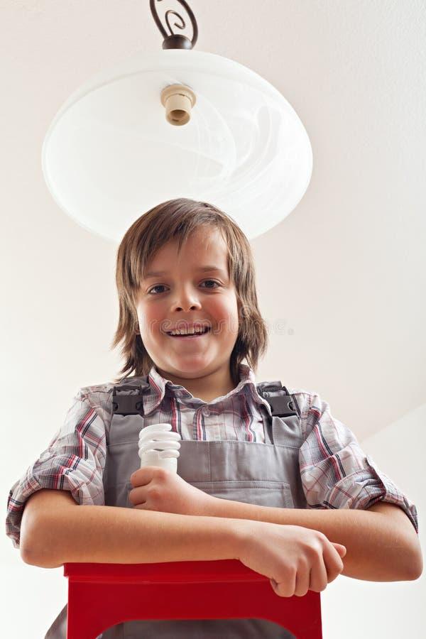 Jongen die lightbulb in plafondlamp veranderen royalty-vrije stock foto's