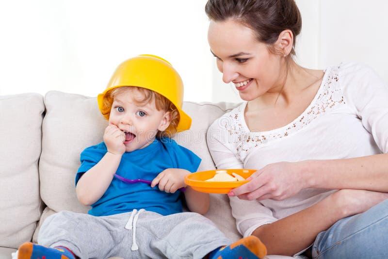 Jongen die maaltijd en zijn mum eten stock afbeeldingen