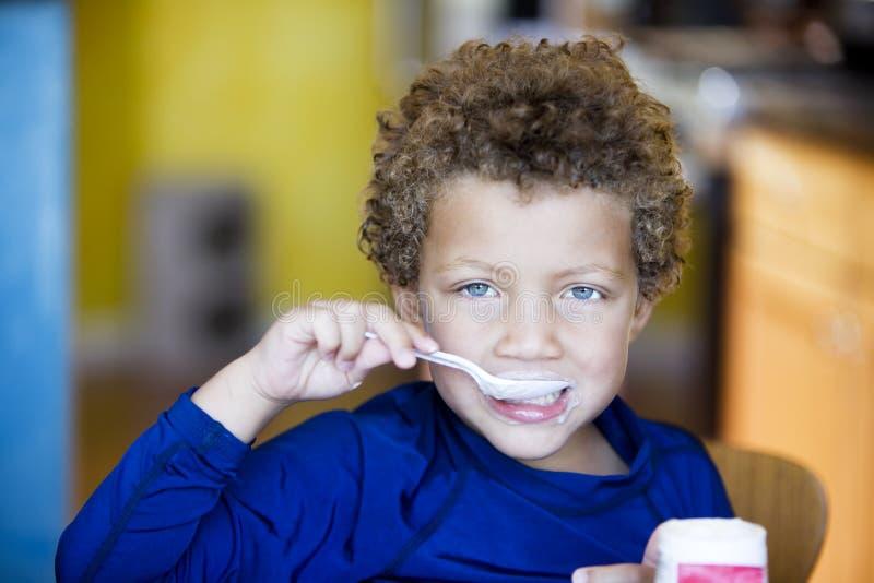 Jongen die met blauwe ogen yoghurt eet royalty-vrije stock foto's