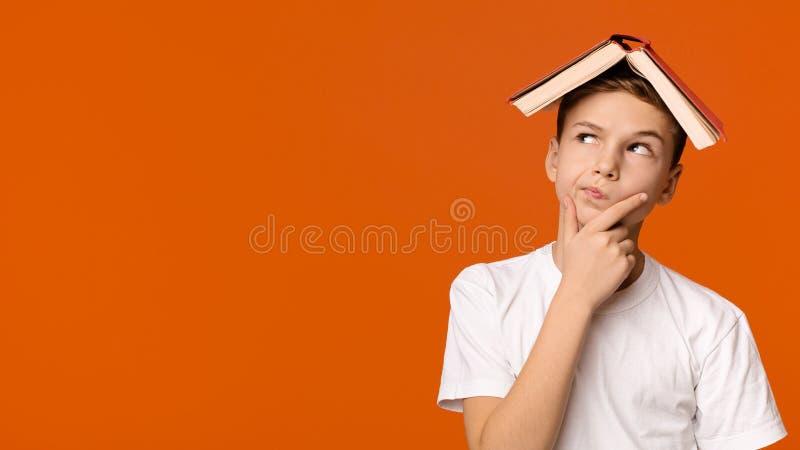 Jongen die met boek op hoofd op oranje achtergrond denken royalty-vrije stock fotografie