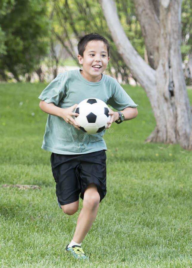 Jongen die met een voetbalbal lopen stock foto