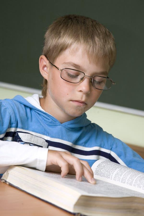 Jongen die met lezing wordt geconcentreerd stock afbeeldingen