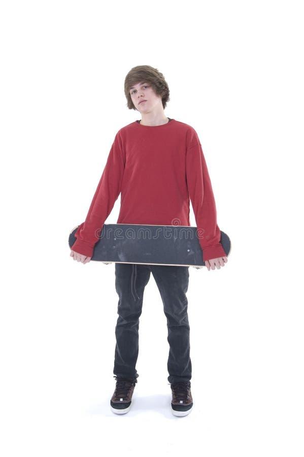 Jongen die met skateboard vooraan wordt gesteld stock fotografie
