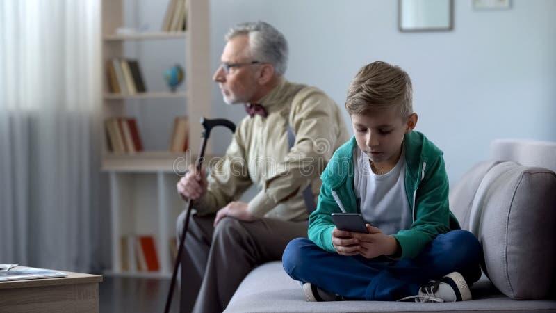 Jongen die mobiele telefoon, verstoorde opazitting met behulp van opzij, Internet-verslavingsconcept royalty-vrije stock afbeeldingen