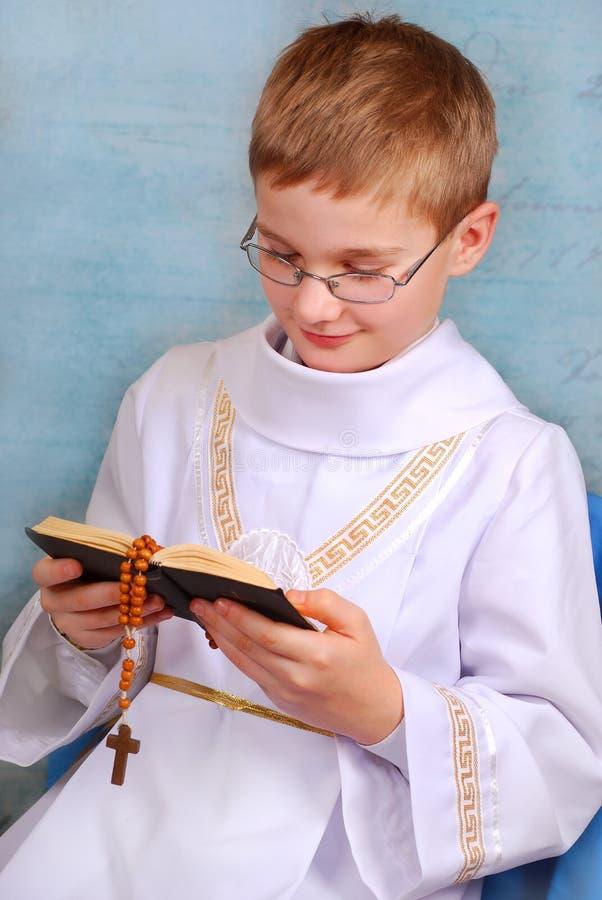 Jongen die naar de eerste heilige kerkgemeenschap met gebedboek gaan stock afbeelding