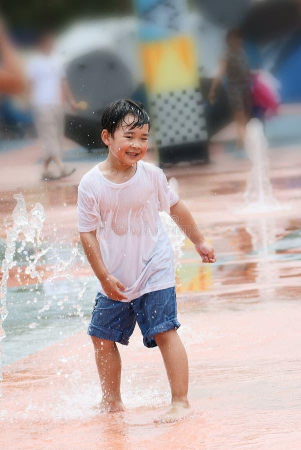 Jongen die nat en in een fonteinvierkant lacht royalty-vrije stock fotografie