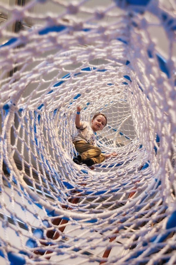 Jongen die in netto koker van pretpark faciliteit beklimmen royalty-vrije stock afbeeldingen