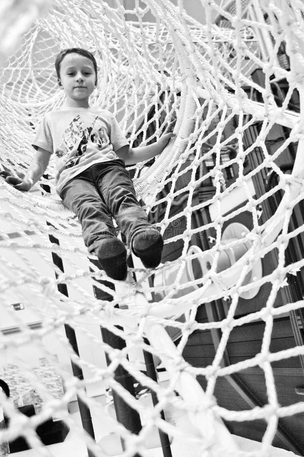 Jongen die in netto koker van pretpark faciliteit beklimmen royalty-vrije stock foto