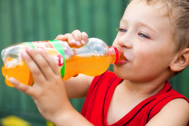 Jongen die ongezonde gebottelde soda drinkt royalty-vrije stock afbeelding