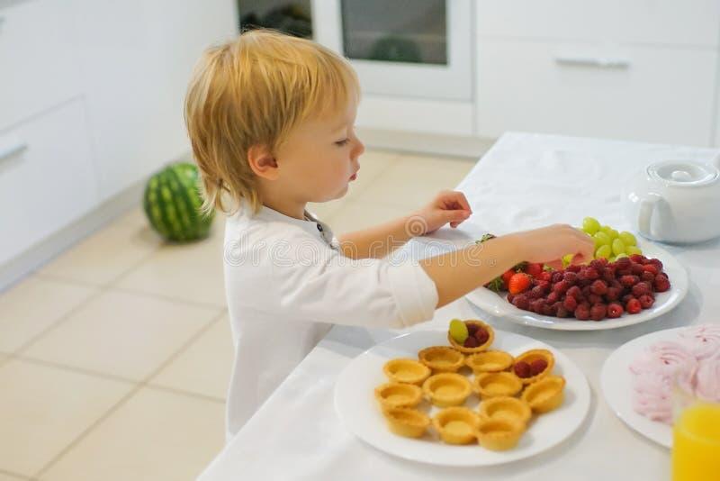 Jongen die ontbijt in witte keuken voorbereiden stock afbeelding