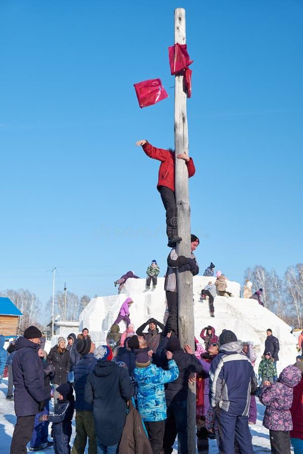 Jongen die op een houten pool voor de prijs, Slavische volksfesti beklimmen royalty-vrije stock foto's