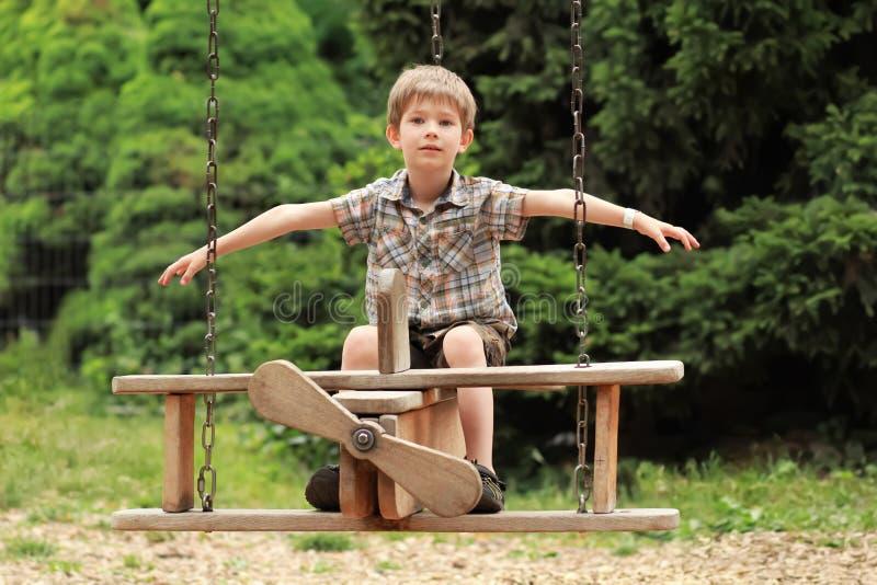 Jongen die op een houten tweedekkerschommeling vliegen in het de zomerpark Het bekijken de camera stock foto's