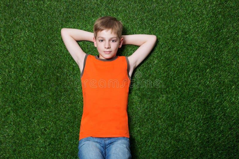 Jongen die op groen gras liggen royalty-vrije stock foto