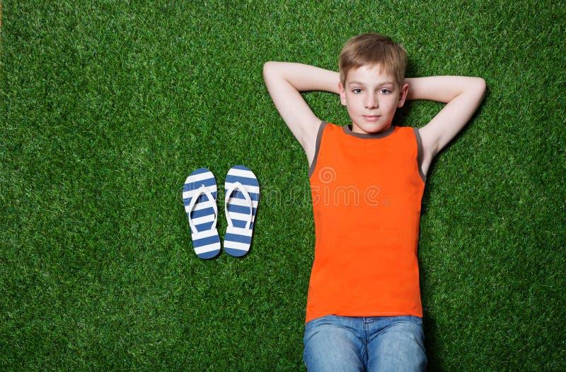 Jongen die op groen gras met pantoffels liggen stock afbeelding