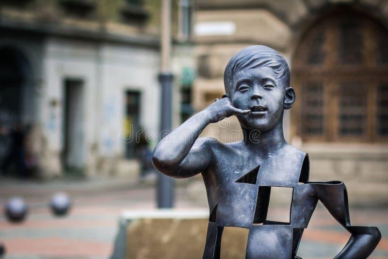 Jongen die op het mobiele beeldhouwwerk van de telefoon moderne kunst in Liberty Square van Timisoara spreken stock foto