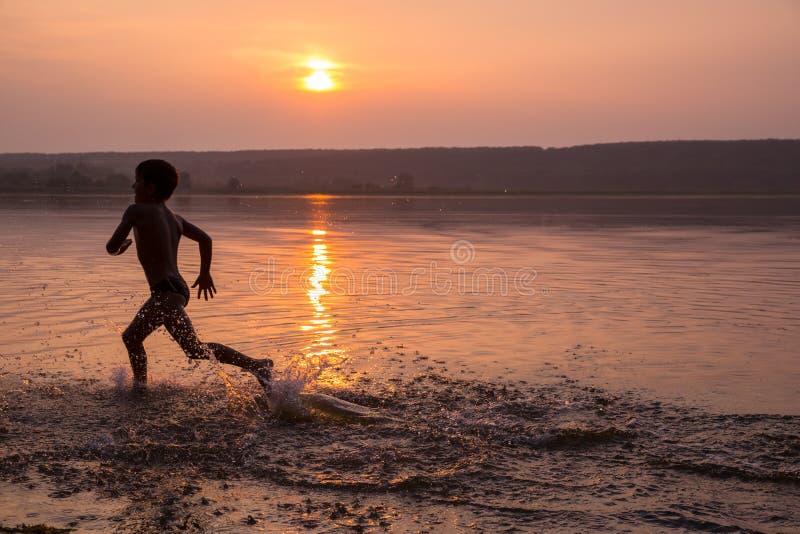 Jongen die op het strand van de rivier tegen zonsondergang lopen stock afbeelding