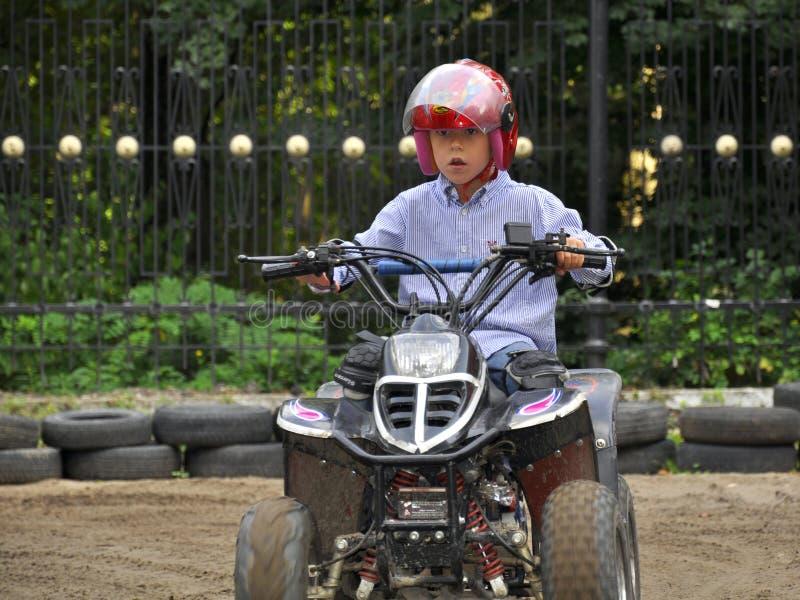Jongen die op jonge geitjes berijdt quadricycle, hebbend pret stock foto