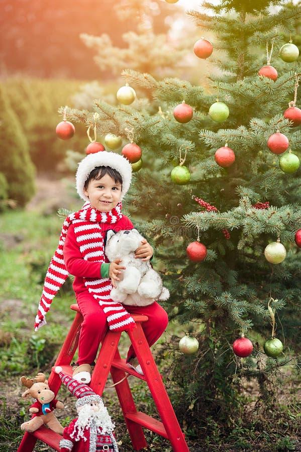 Jongen die op Kerstmis in het hout wachten Kerstmis in juli stock afbeeldingen