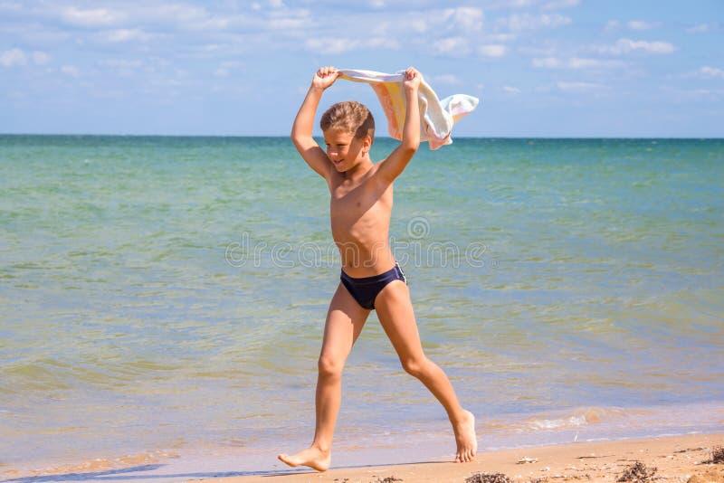 Jongen die op kustlijn met handdoek lopen stock fotografie
