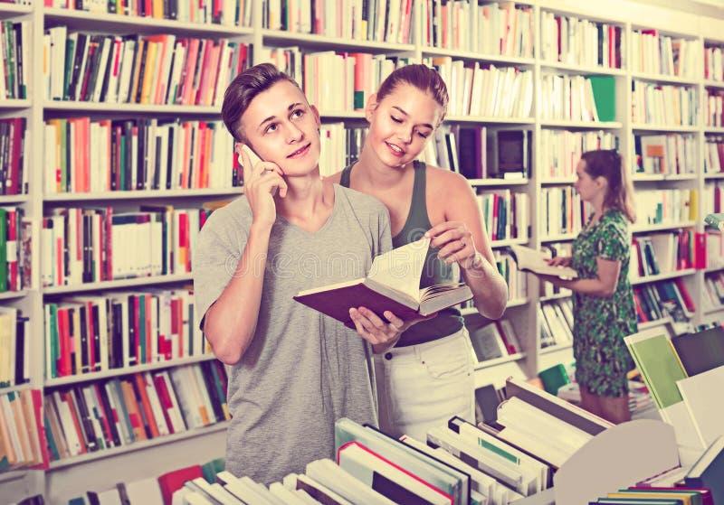 Jongen die op mobiele telefoon spreken terwijl het kopen van boeken met vriend in st royalty-vrije stock afbeelding