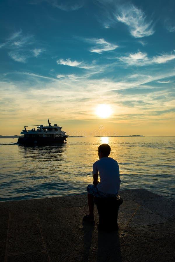 Jongen die op Pier Verlatend Schip bij Zonsondergang letten op royalty-vrije stock afbeelding