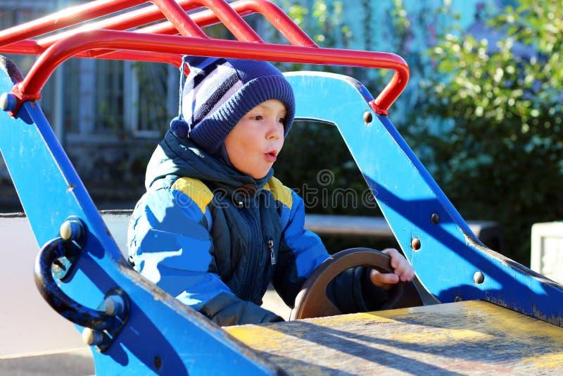 Jongen die op schommelingsauto's slingeren, Speelplaats royalty-vrije stock foto's