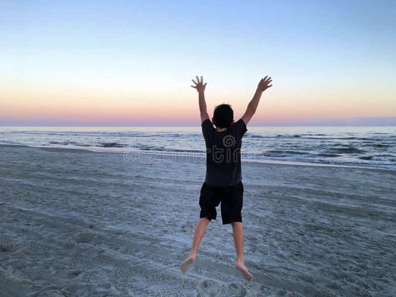 Jongen die op strand springt stock afbeelding