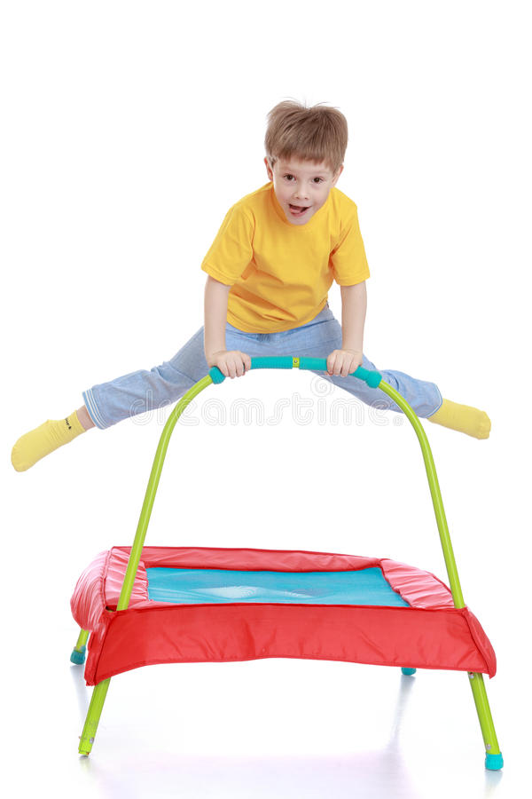 Jongen die op trampoline springen stock foto